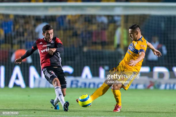Juninho of Tigres fights for the ball with Juan Pablo Vigon of Atlas during the 8th round match between Tigres UANL and Atlas as part of the Torneo...