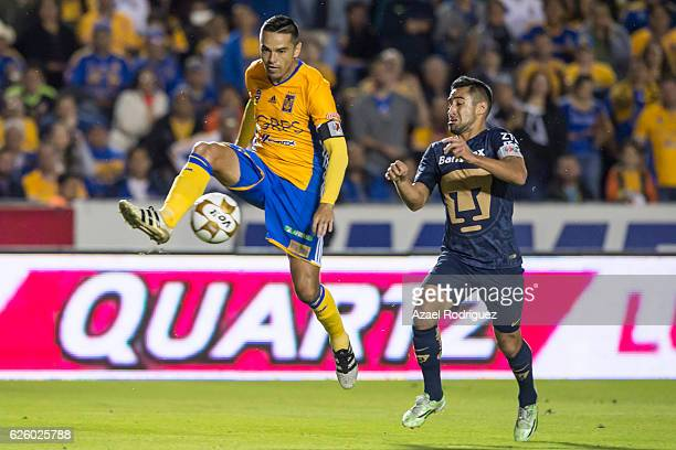 Juninho of Tigres fights for the ball with Luis Fuentes of Pumas during the quarter finals second leg match between Tigres UANL and Pumas UNAM as...