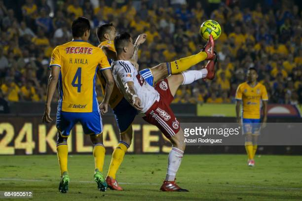 Juninho of Tigres fights for the ball with Milton Caraglio of Tijuana during the semi finals first leg match between Tigres UANL and Tijuana as part...