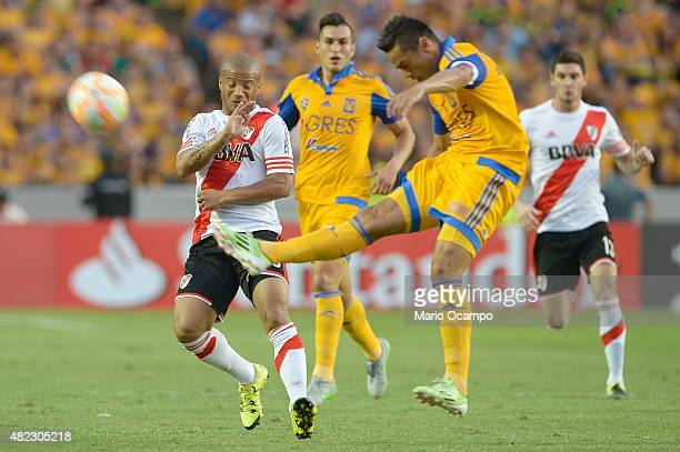 Juninho of Tigres kicks the ball in front of Carlos Sanchez of River Plate Plate during a first leg final match between Tigres UANL and River Plate...