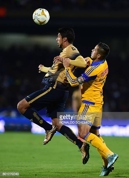 Juninho of Tigres marks Eduardo Herrera of Pumas during the final match of the Mexican Apertura football tournament at the Universitario stadium in...