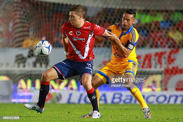 Juninho of Tigres struggles for the ball with Julio Cesar Furch of Veracruz during the 16th round match between Veracruz and Tigres UANL as part of...