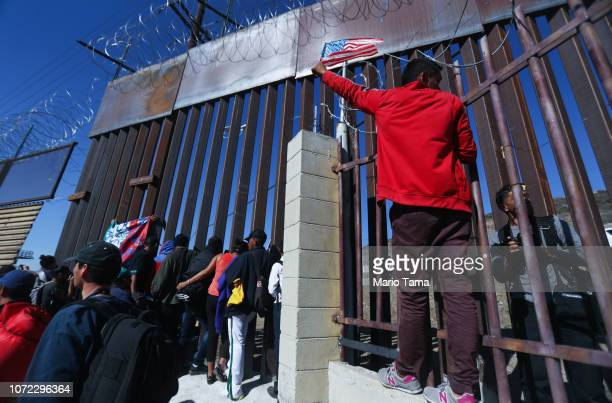 Junior a migrant from Honduras waves the American flag while standing with other migrants at the USMexico border fence on November 25 2018 in Tijuana...