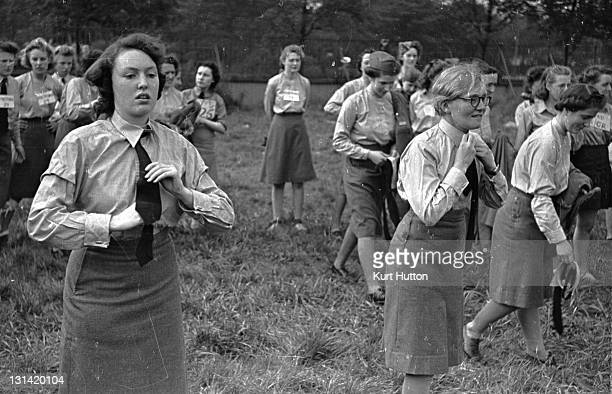 Junior Air Corps members attending a Girl's Rally at Belle Vue Manchester take off their ties to be followed by their collars and caps They will then...