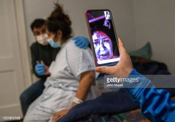 Junior allows his grandmother to watch on a video call as his mother Zully a Guatemalan asylum seeker also suffering from COVID19 and father Marvin...