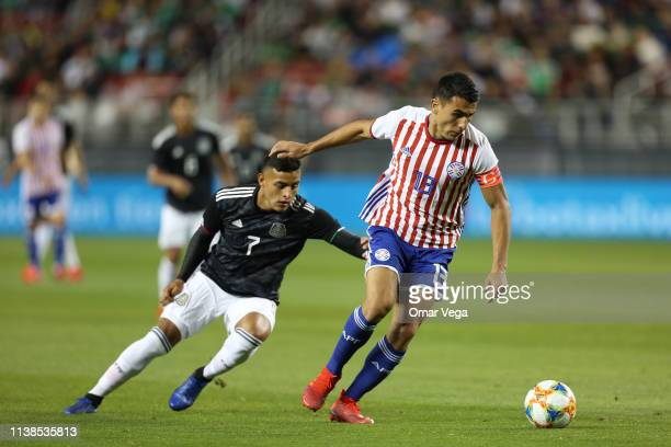 Junior Alonso of Paraguay and Alexis Vega of Mexico fight the ball during the friendly match between Paraguay and Mexico at Levi's Stadium on March...