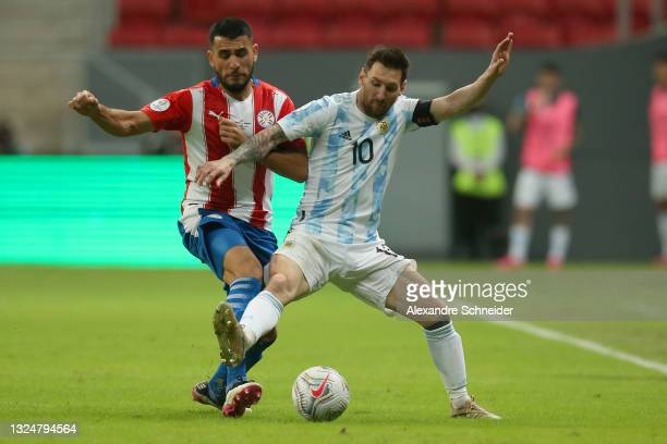 Junior Alonso of Paraguay competes for the ball with Lionel Messi of Argentina during a group A match between Argentina and Paraguay as part of...