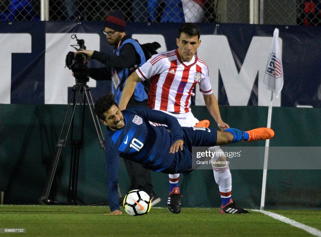 Junior Alonso #13 of Paraguay draws a yellow card as he trips Kenny Saief #10 of United States during their game at WakeMed Soccer Park on March 27, 2018 in Cary, North Carolina. The United States won 1-0.