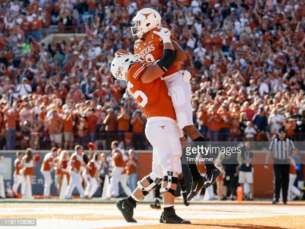 Junior Angilau of the Texas Longhorns congratulates Collin Johnson after a touchdown reception in the first half against the Kansas State Wildcats at...