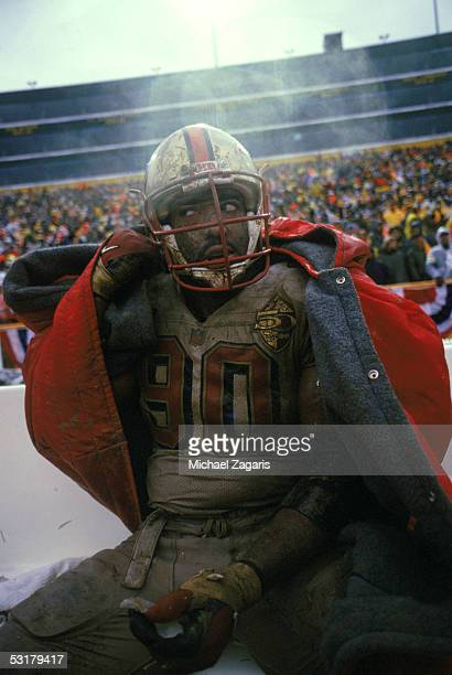 Junior Bryant of the San Francisco 49ers sits on the sideline with his uniform covered in mud against the Green Bay Packers during the 1996 NFC...