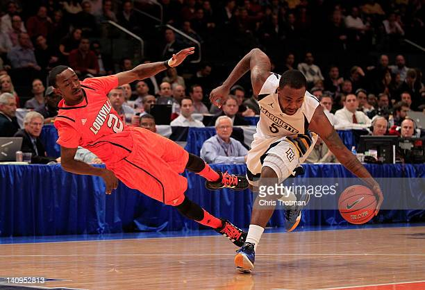 Junior Cadougan of the Marquette Golden Eagles and Russ Smith of the Louisville Cardinals dive for a loose ball during the quarterfinals of the Big...