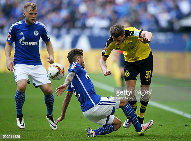 Junior Caicara and Johannes Geis of FC Schalke 04 battle for the ball with Erik Durm of Borussia Dortmund during the Bundesliga match between FC...