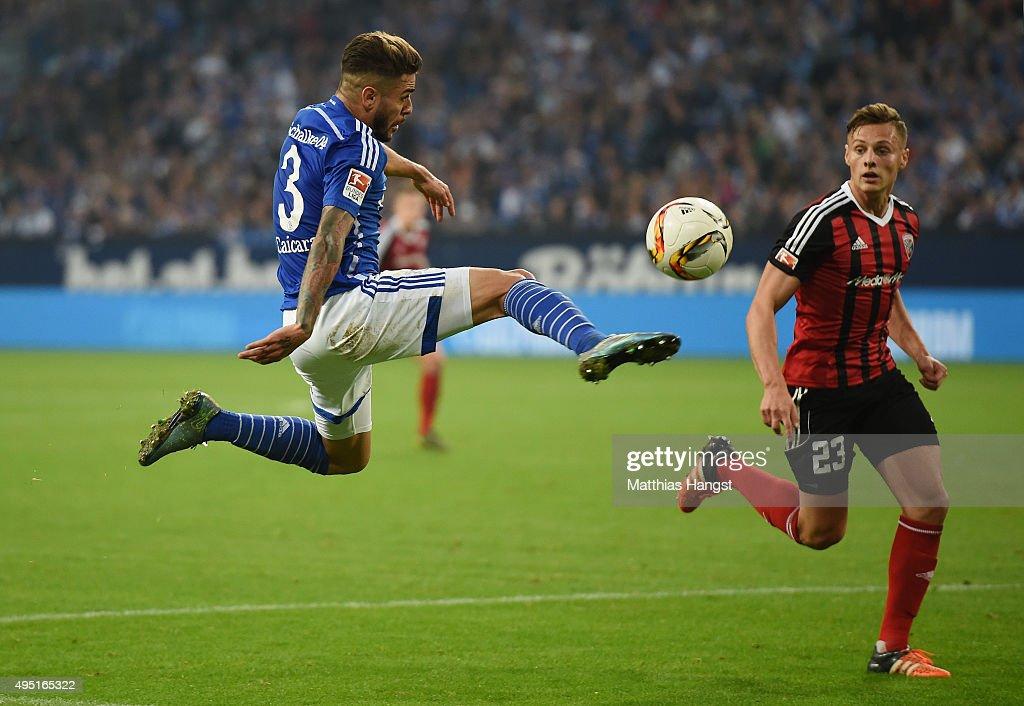 Junior Caicara of Schalke plays a pass against Robert Bauer of Ingolstadt during the Bundesliga match between FC Schalke 04 and FC Ingolstadt at Veltins-Arena on October 31, 2015 in Gelsenkirchen, Germany.
