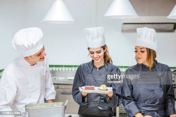 junior chef showing her prepaired dessert on plate - コック帽 ストックフォトと画像