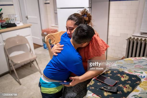 Junior comforts his mother Zully after they spoke on the phone with her Covidsick mother Aurora on June 17 2020 in Stamford Connecticut Aurora who...