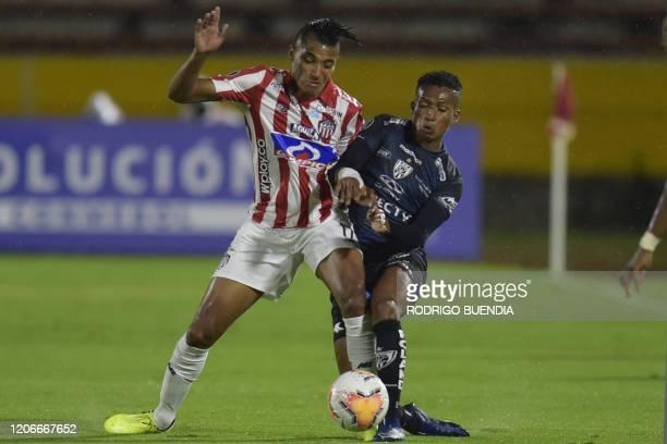 Junior de Barranquilla's defender Gabriel Fuentes and Ecuador's Independiente del Valle player Fernando Guerrero vie for the ball during their Copa...