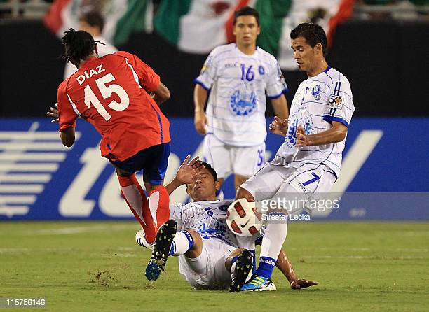 Junior Diaz of Costa Rica slides into Victor Turcios and teammate Ramon Sanchez of El Salvador during their game in the CONCACAF Gold Cup at Bank of...