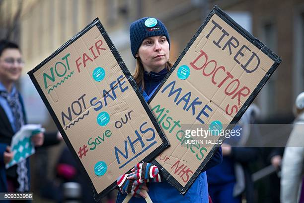 A junior doctor holds placards as they protest outside Guy's Hospital during a 24hour strike over pay and conditions in London on February 10 2016...