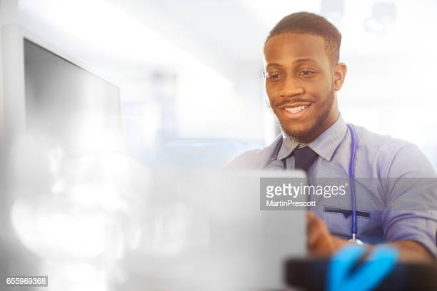 junior doctor smiling as he works at his desk - junior doctor stock pictures, royalty-free photos & images