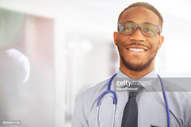 junior doctor smiling to camera in hospital - male doctor stock photos and pictures