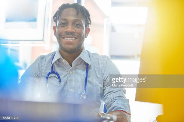 junior doctor smiling to camera - junior doctor stock pictures, royalty-free photos & images