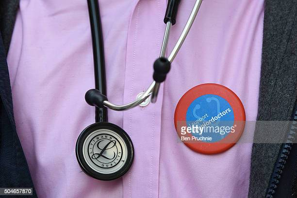 A junior doctor wears a stethoscope and a badge with the slogan I support #juniordoctors outside Guy's hospital as junior doctors stage a 24hour...
