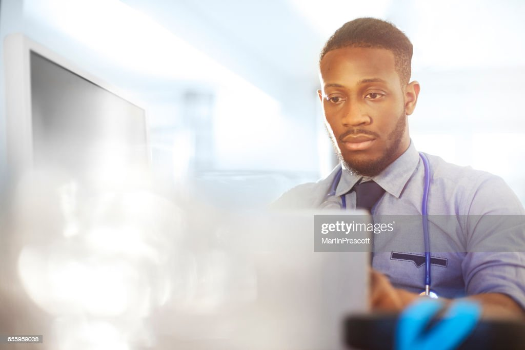 Junior doctor working at his desk in his office : Stock Photo