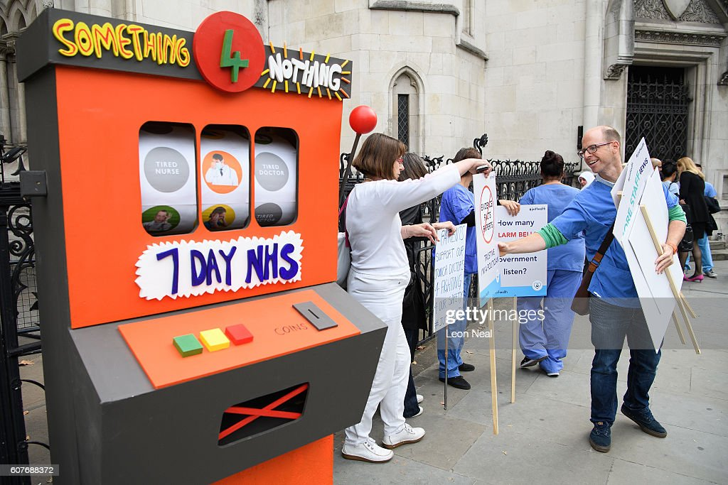 Junior doctors and supporters stand with a fake slot machine outside the Royal Courts of Justice, Strand on the first day of their hearing as they challenge the government's plan for a seven-day NHS service, on September 19, 2016 in London, England. Justice for Health was founded in March 2015 by five frontline junior doctors to mount a legal challenge against the proposals by Jeremy Hunt, the Secretary of State for Health, to provide a full NHS service over the weekend, despite claims by opponents that the plan is under-funded and has not been fully considered.