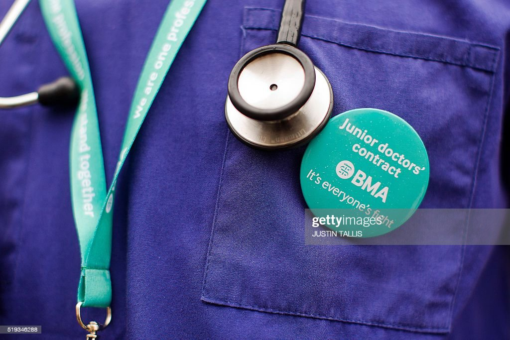 Junior doctors protest outside St Thomas' Hospital in central London on April 6, 2016, against proposed new conditions and pay rates for working unsociable hours. Thousands of operations and procedures across England have been cancelled as a result of the 48 hour strike which began Wednesday morning. / AFP / JUSTIN