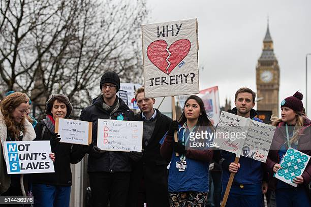 Junior doctors protest with banners outside St Thomas' Hospital in central London on March 9 against proposed new conditions and pay rates for...