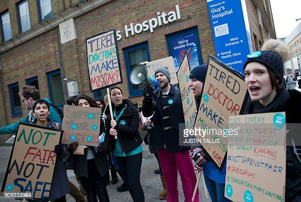 Junior doctors shout slogans and hold placards as they protest outside Guy's Hospital during a 24hour strike over pay and conditions in London on...