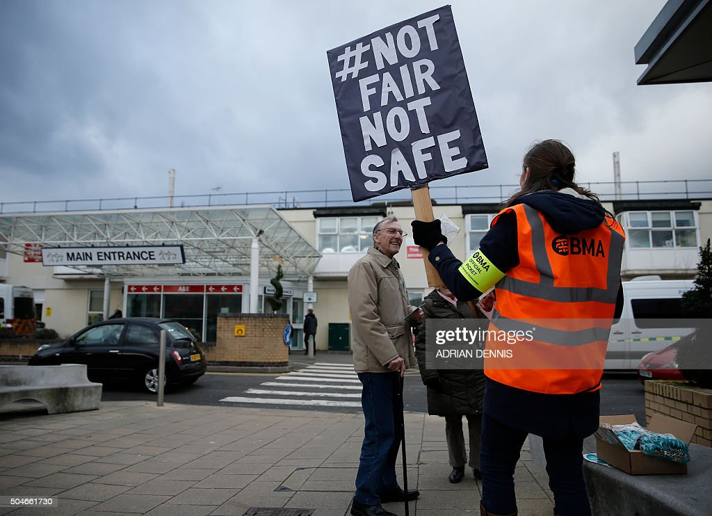 Junior doctors stand on a picket line outside the Frimley Park Hospital in Frimley, south west of London, on January 12, 2016, during a strike by junior doctors. Tens of thousands of junior doctors in England went on strike Tuesday, causing major disruption to hospitals across the country in the first walkout of its kind for 40 years. The strike is over a new type of contract which the government says will improve healthcare at night and at weekends but medics say would drastically reduce their pay.