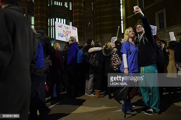 Junior doctors take a selfie photo as they join demonstrators outside the Department of Health on Whitehall in central London on February 11 to...