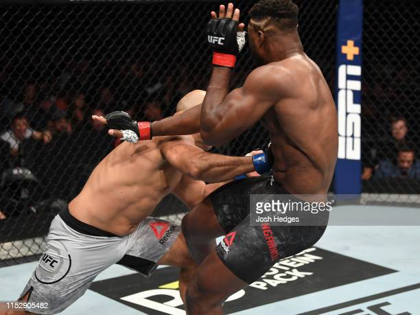 Junior Dos Santos of Brazil punches Francis Ngannou of Cameroon in their heavyweight bout during the UFC Fight Night event at the Target Center on...