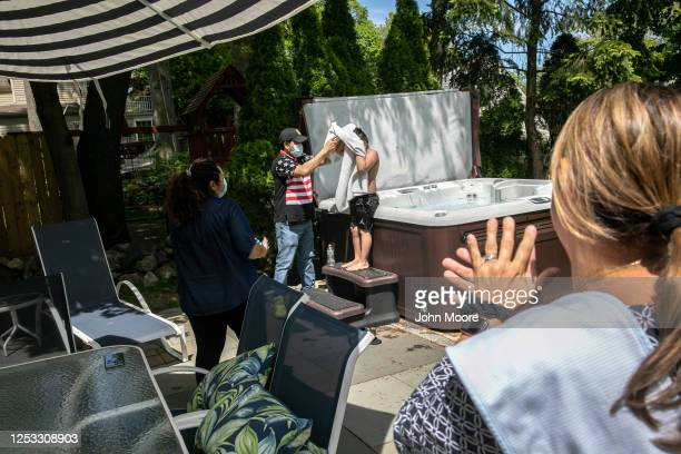 Junior dries off after swimming in his elementary school teacher Luciana Lira's jacuzzi on May 20 2020 in Stamford Connecticut His Guatemalan...