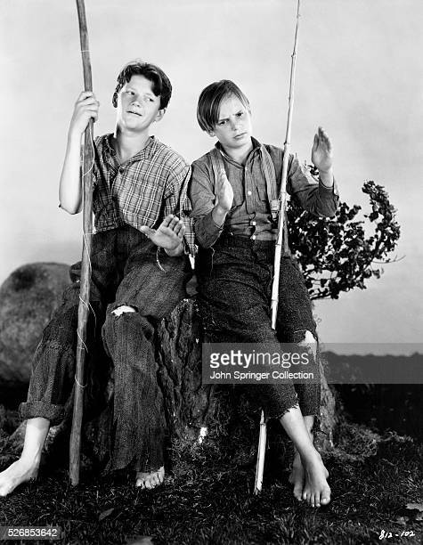 Junior Durkin and Jackie Coogan tell fish stories as they play the roles of Huckleberry Finn and Tom Sawyer in the 1930 film Tom Sawyer