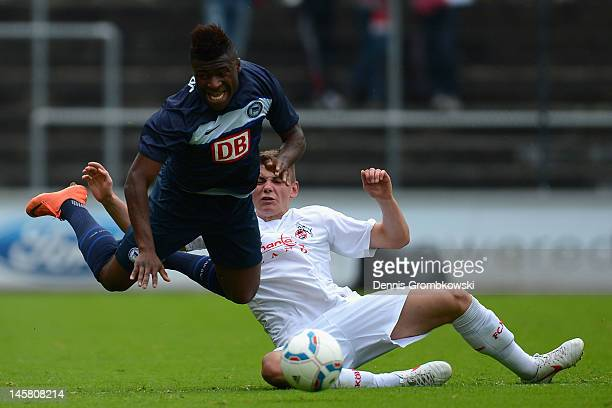 Junior EbotEtchi of Berlin is brought down by Andre Wallenborn of Cologne during the B Juniors Bundesliga semi final match between 1 FC Koeln and...