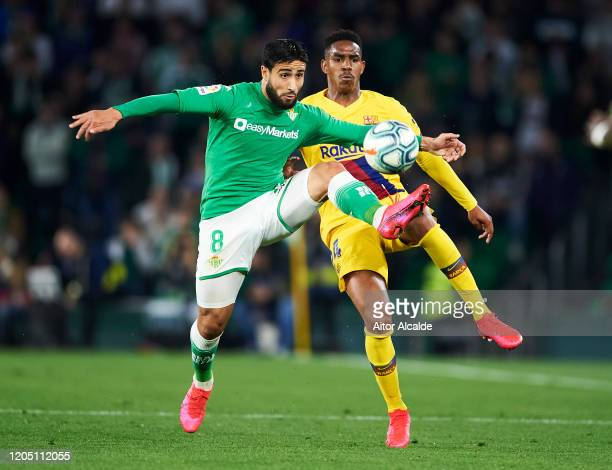Junior Firpo of FC Barcelona duels for the ball with Nabil Fekir of Real Betis Balompie during the Liga match between Real Betis Balompie and FC...