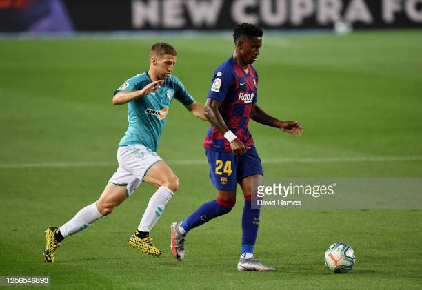 Junior Firpo of FC Barcelona is challenged by Darko Brasanac of Osasuna during the Liga match between FC Barcelona and CA Osasuna at Camp Nou on July...