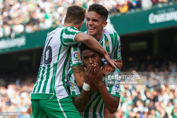 Junior Firpo of Real Betis Balompie celebrates after scoring with Marc Bartra of Real Betis Balompie and Loren Moron of Real Betis Balompie during...