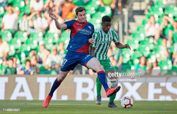 Junior Firpo of Real Betis competes for the ball with Alex Gallar of SD Huesca during the La Liga match between Real Betis Balompie and SD Huesca at...