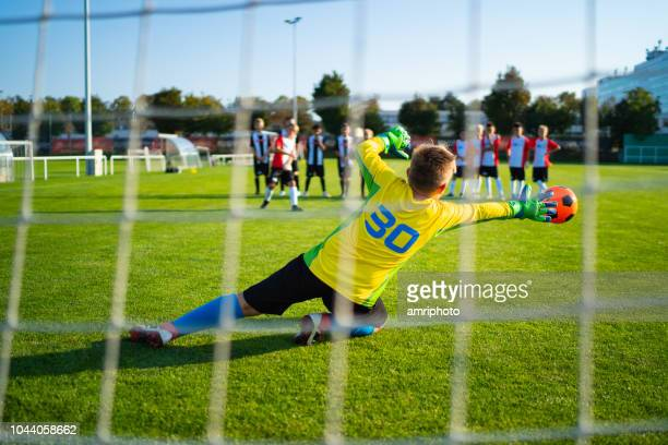 junior football soccer game goalie in action - shootout stock pictures, royalty-free photos & images