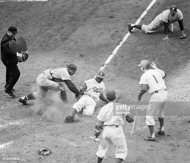 Junior Gilliam of the Dodgers slides past Phillie catcher Any Seminick's tag to score on his inside the park homer in the fourth inning of the...