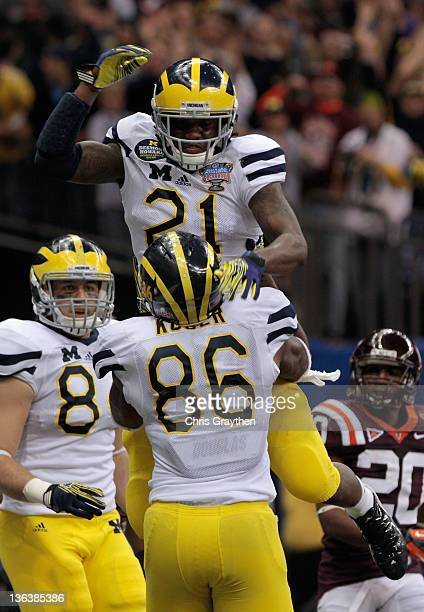 Junior Hemingway and Kevin Koger of the Michigan Wolverines celebrate after Hemingway scored a 18yard touchdown reception in the third quarter...