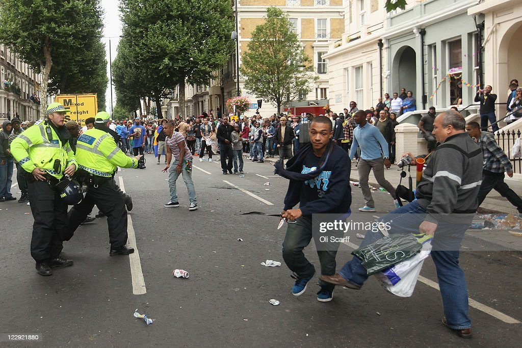 Junior Henry avoids being tripped by a member of the public as he runs down the road with a knife, having stabbed Rio Andre at the Notting Hill Carnival on August 29, 2011 in London, England. The annual carnival, which is the largest of its kind in Europe and is expected to attract around 1 million revellers, has taken place every August Bank Holiday since 1966.