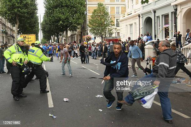 Junior Henry avoids being tripped by a member of the public as he runs down the road with a knife having stabbed Rio Andre at the Notting Hill...