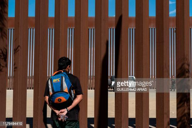 Junior Hernandez, a migrant from Guatemala, looks on to a border patrol through the border fence at the Mexican side of the US-Mexico border in...