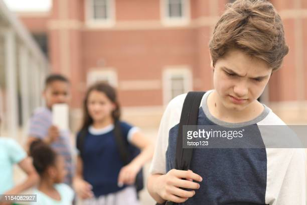 junior high age boy being bullied at school. - veto stock pictures, royalty-free photos & images