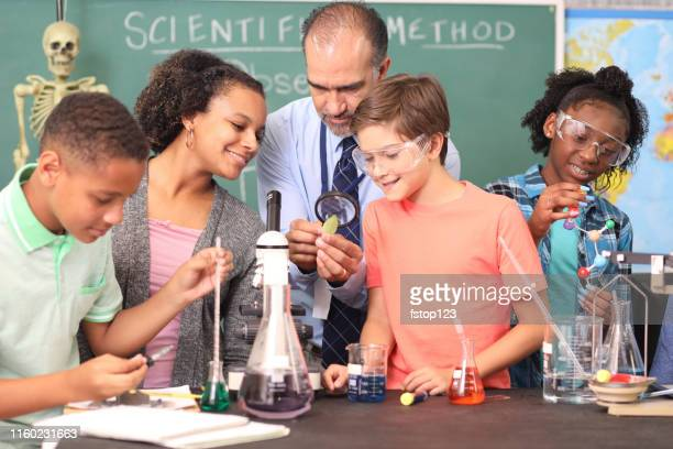 junior high age school students conduct science experiments in classroom. - junior high student stock pictures, royalty-free photos & images