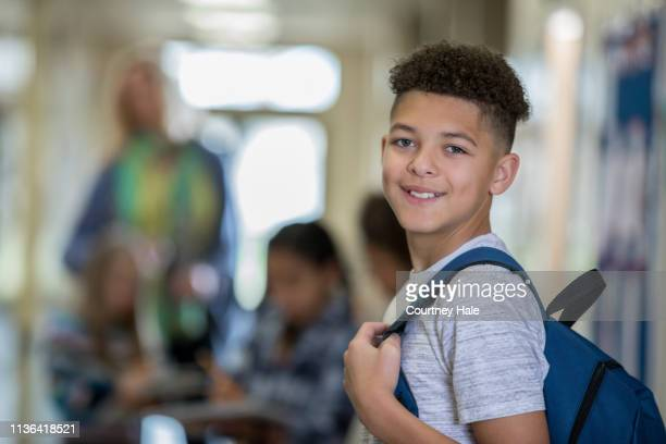 junior high school boy smiles at the camera while walking to class in hallway - junior high student stock pictures, royalty-free photos & images